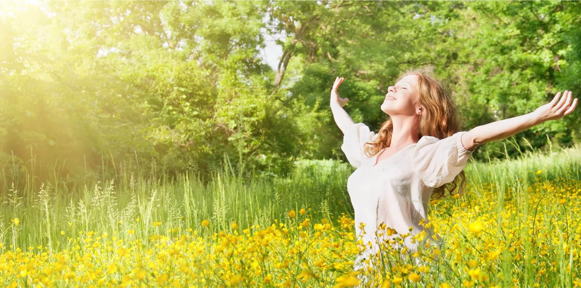 Eine glückliche junge Frau auf dem Feld in den Sonnenstrahlen